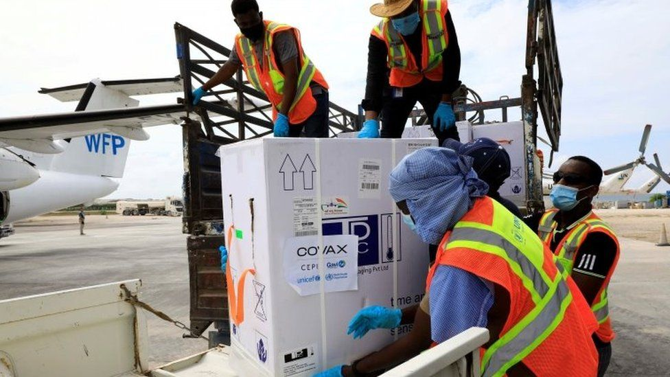 Workers offload AstraZeneca/Oxford vaccines under the COVAX scheme at the Aden Abdulle Osman Airport in Mogadishu, Somalia