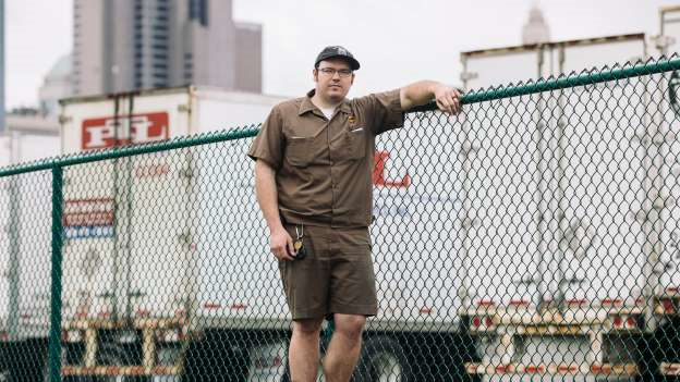 "a man standing in front of a fence: ""I didn't think I'd be on the front line of the pandemic,"" said Nick Perry, a UPS driver in Columbus, Ohio."