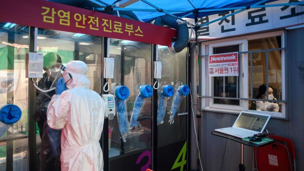 A man speaks to a nurse during a COVID-19 novel coronavirus test at a testing booth outside Yangji hospital in Seoul in March 2020